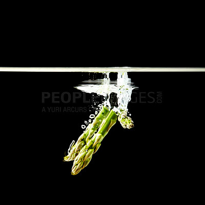 Buy stock photo Stalks of asparagus falling into water against black background