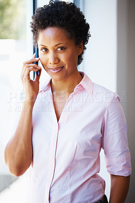 Buy stock photo African American business woman using cell phone near glass window