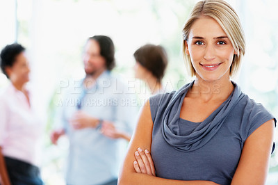 Buy stock photo Young woman standing with arms crossed with people in background