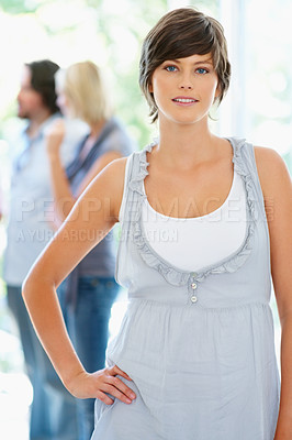 Buy stock photo Woman standing with hand on hip while people talk in background