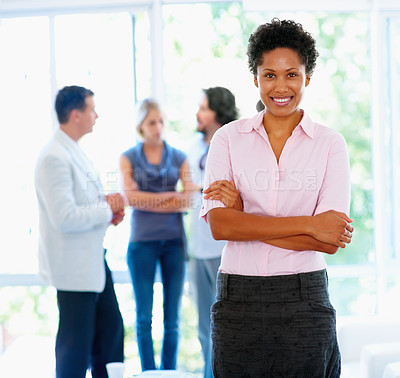 Buy stock photo Woman standing with arms crossed with group in background