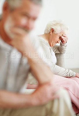 Buy stock photo Shot of a unhappy senior woman with her husband in the foreground