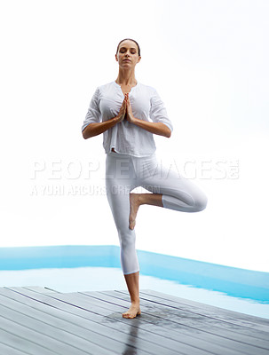 Buy stock photo Shot of a gorgeous young woman doing yoga outdoors beside a pool