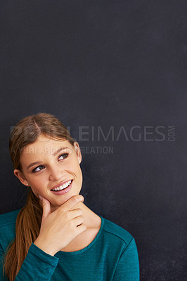 Buy stock photo Shot of a beautiful young woman standing against a blackboard