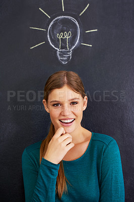 Buy stock photo Cropped shot of an attractive young woman standing in front of a blackboard
