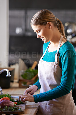Buy stock photo Shot of an attractive young woman chopping vegetables in the kitchen