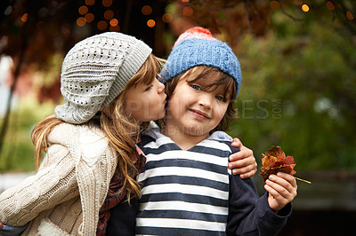 Buy stock photo A cute little boy looking shy as his sister kisses his cheek