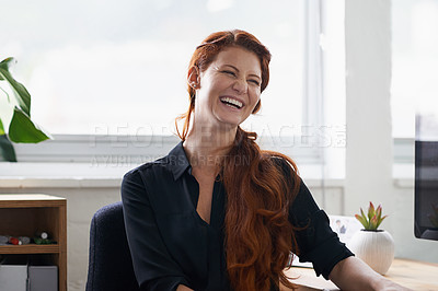 Buy stock photo Shot of a happy young businesswoman sitting at her desk