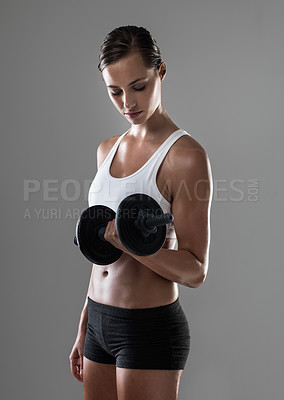 Buy stock photo Studio shot of an athletic woman lifting weights during her daily workout