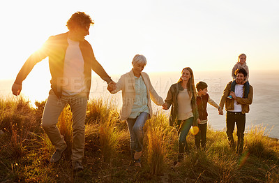 Buy stock photo A multi-generational family walking up a grassy hill together at sunset with the ocean in the background