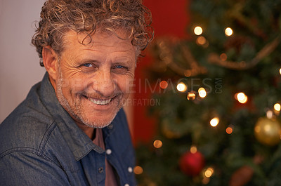 Buy stock photo Portrait of a mature man sitting beside a Christmas tree