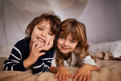 Buy stock photo Portrait of two adorable siblings lying underneath a fort