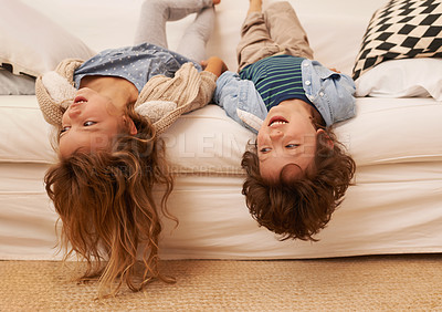 Buy stock photo Shot of two young children lying on a sofa with their heads hanging over the edge