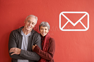 Buy stock photo Portrait of a happy senior couple standing in front of a red background with a vector symbol for mail