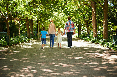 Buy stock photo A rear view shot of a family walking hand in hand through a beautiful park
