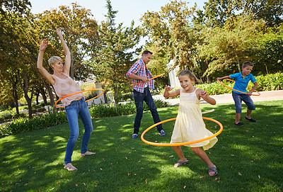 Buy stock photo A happy family hula hooping in the park on a sunny day