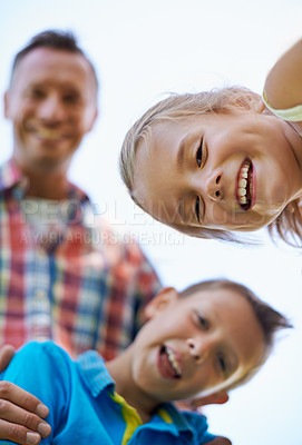 Buy stock photo A low angle portrait of a happy two happy kids and their dad spending the day outdoors