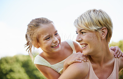 Buy stock photo A cropped shot of a happy mother giving her young daughter a piggyback ride