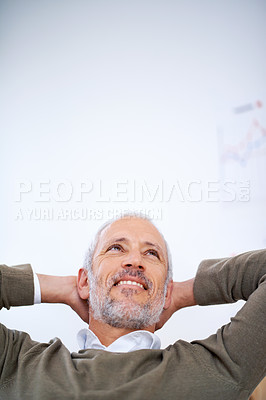 Buy stock photo A relaxed and carefree businessman sitting at his desk