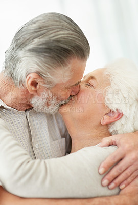Buy stock photo Shot of an elderly couple hugging and kissing each other