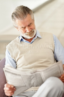 Buy stock photo Shot of a semior man sitting in a chair and reading a newspaper at home