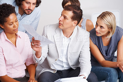 Buy stock photo Leader discussing paper work with his team