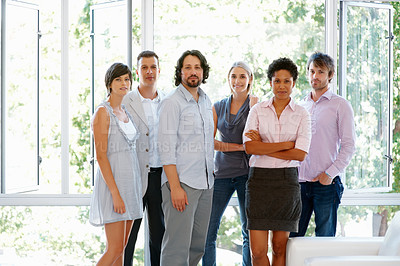 Buy stock photo Young and attractive business executives standing together at office