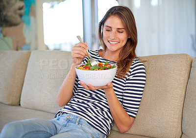 Buy stock photo Shot of a young woman eating a bowl full of salad on her sofa at home