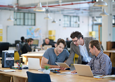 Buy stock photo Shot of business colleagues discussing matters with the help of wireless technology in their office