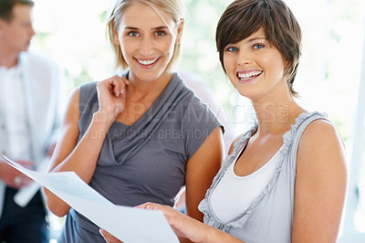 Buy stock photo Pretty female executives holding documents with man in background
