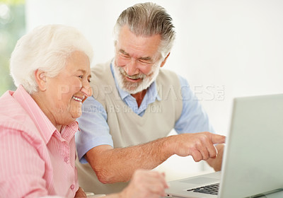 Buy stock photo Shot of a senior couple laughing while working on a laptop