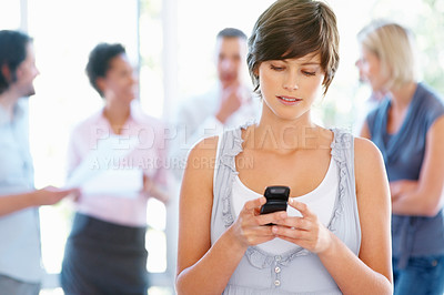 Buy stock photo Young woman sending text message with people in background