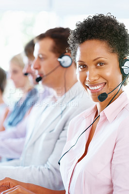 Buy stock photo Portrait of female call center executive in headphones with team in blur background