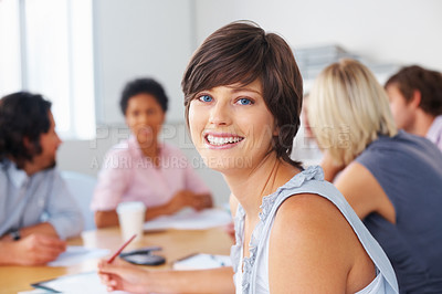 Buy stock photo Beautiful woman taking notes while looking at you in meeting