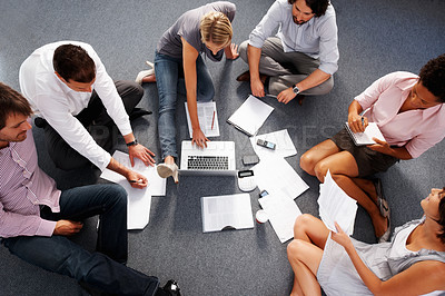 Buy stock photo Top view of businesspeople sitting on the floor and discussing projects