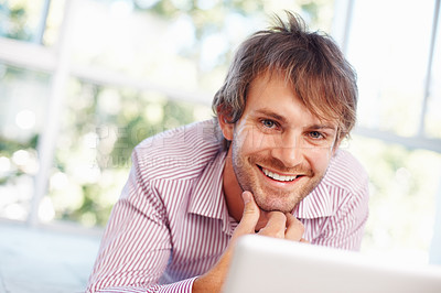 Buy stock photo Smiling business man lying down with the laptop
