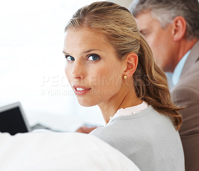 Buy stock photo Young businesswoman looking confidently with her business colleagues at meeting