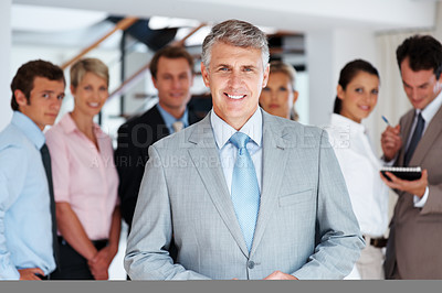 Buy stock photo Happy senior manager standing and his colleague behind him at office