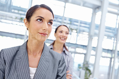 Buy stock photo Attractive young businesswoman with her coworker standing behind her as they look away