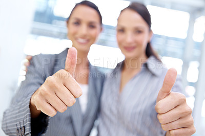 Buy stock photo Happy young businesswomen smiling together and giving the thumb's up gesture - portrait