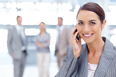 Buy stock photo Smiling young businesswoman using her mobile while at work