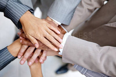 Buy stock photo Cropped view of a group of businesspeople putting their hands in together to show solidarity
