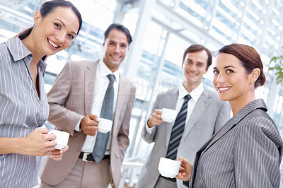 Buy stock photo Smiling office coworkers enjoying some coffee together while on their break