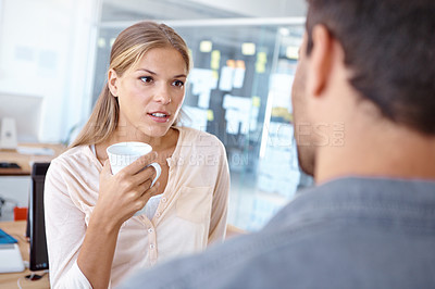 Buy stock photo Cropped shot of two young business professionals talking over a cup of coffee