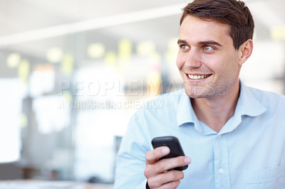 Buy stock photo Shot of a smiling young business professional sending a text message on his mobile phone