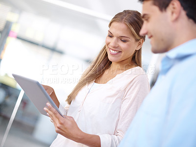 Buy stock photo Low angle shot of two young businesspeople working on a digital tablet
