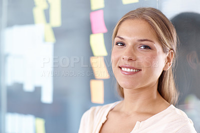 Buy stock photo Beautiful young businesswoman leaning against a glass wall with post-it notes stuck to it - portrait