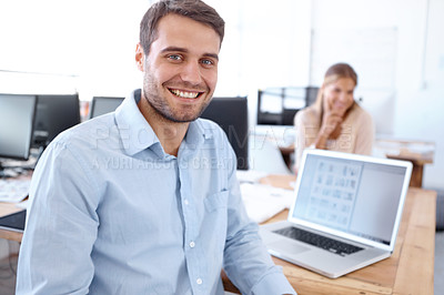 Buy stock photo Handsome young businessman sitting at his desk with his co-worker in the background - portrait