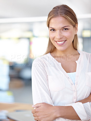 Buy stock photo Beautiful young woman smiling at the camera with her arms folded while standing in an office