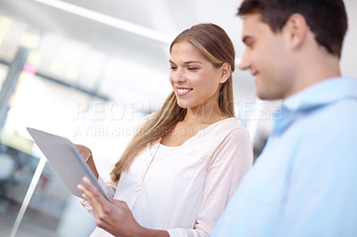 Buy stock photo Two young businesspeople working on a digital tablet and smiling - copyspace